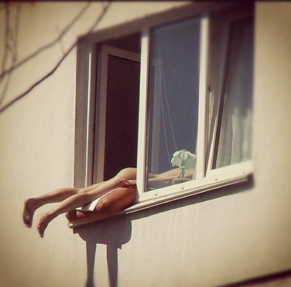 Prende il sole nuda col sedere fuori dalla finestra