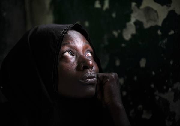 Miseria e fame a Mogadiscio, occhi disperati nella penombra -