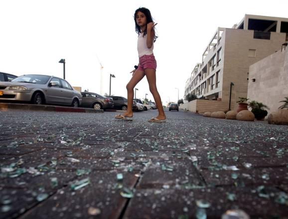 Gaza, una ragazzina passeggia davanti a una vetrina mandata in frantumi dall'esplosione di un razzo