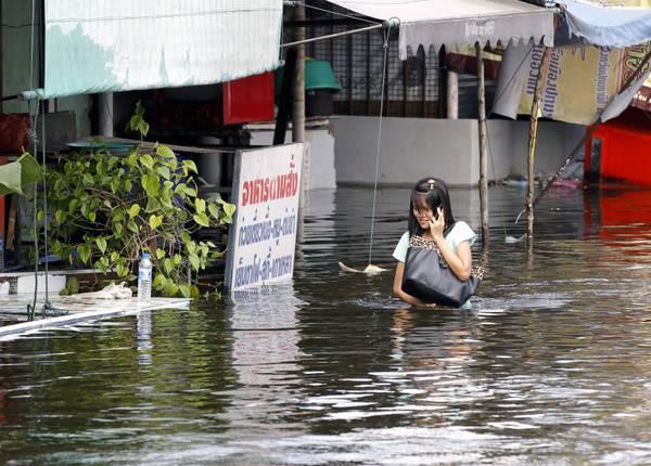 Una ragazza thailandese parla al telefono mentre attraversa una strada del suo villaggio completamen