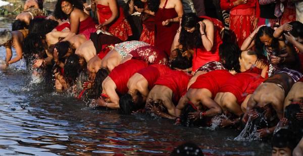 In Nepal, le donne si immerogono in rosso nel fiume Hanumante per avere un buon marito